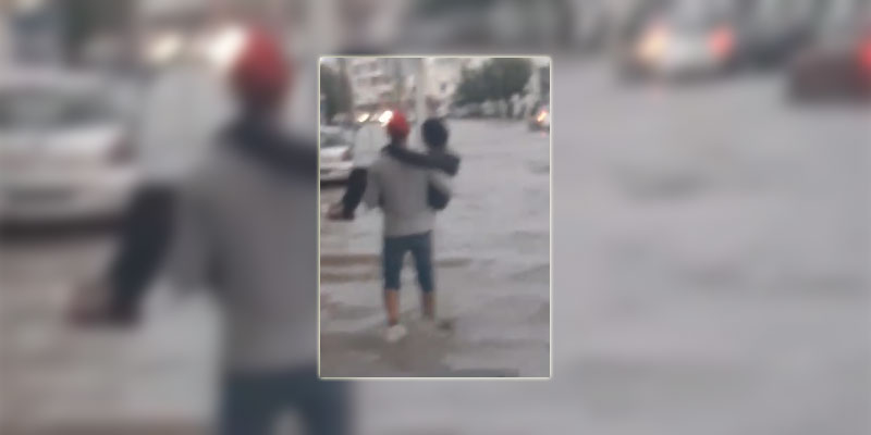 بالفيديو، رجل يحمل إمراة و يعبر بها الطريق المغمورة بالمياه و التعاليق ''يحيا الحب...''